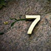 The number 7 on a stone representing 7 facts about Online Exams